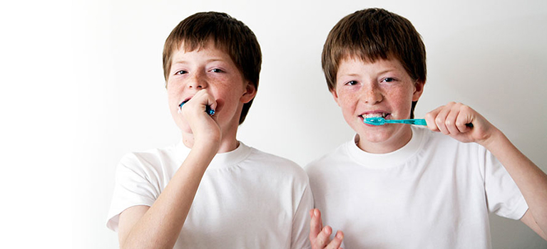 Twins brushing teeth
