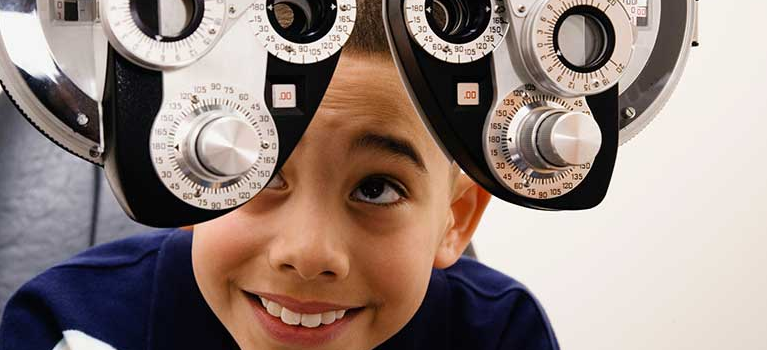 Boy looking at eye examination equipment