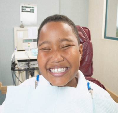 boy smiling in dentist's chair