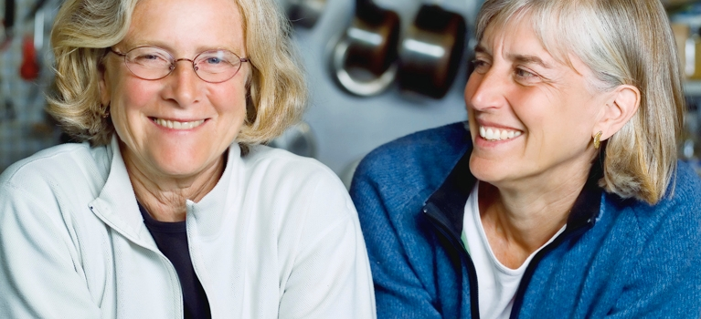 Two mature women lean on kitchen counter smiling