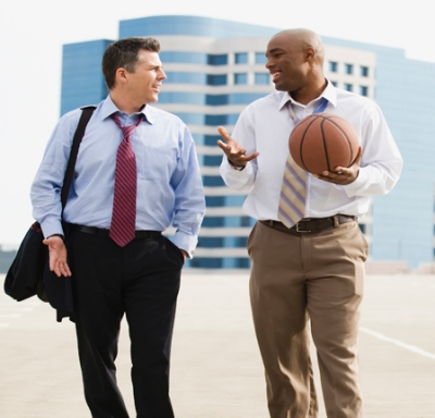 Two businessmen in parking lot carrying basketball