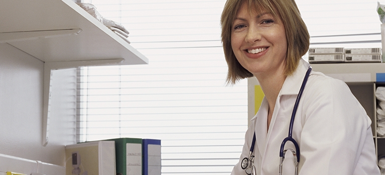 Nurse smiling at camera while sitting at desk