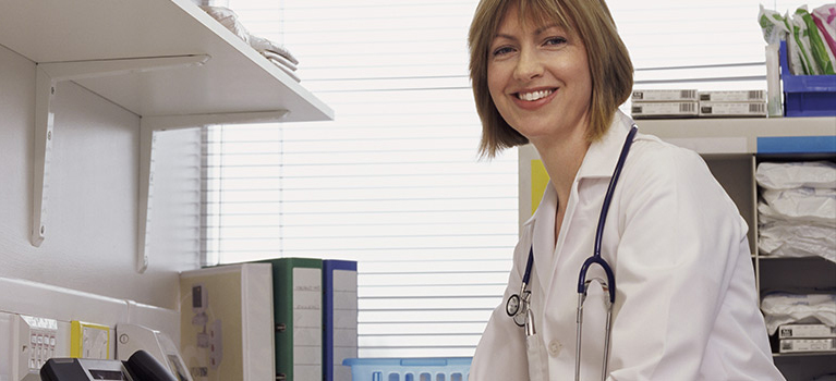 Nurse sitting at desk smiling