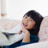 Child laughing with newspaper