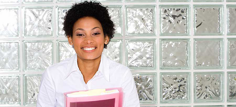 Young businesswoman smiling in front of glass wall