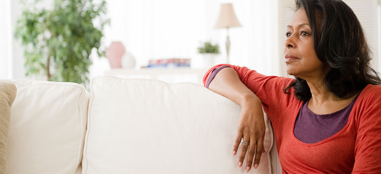 Woman on couch looking into the distance
