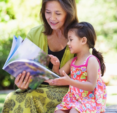Woman and granddaughter looking at book