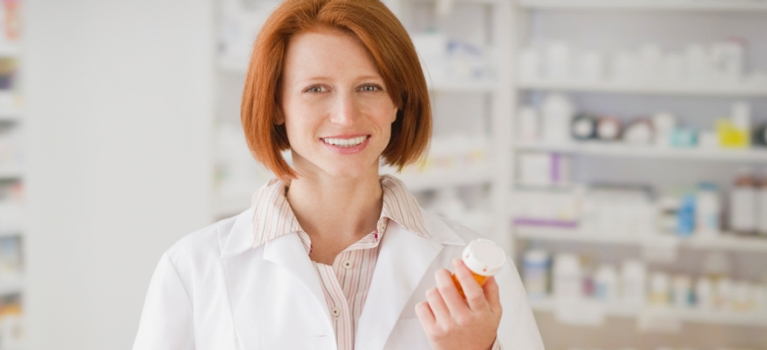 Pharmacist holding pill bottles