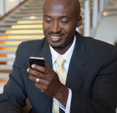 Smiling businessman texting