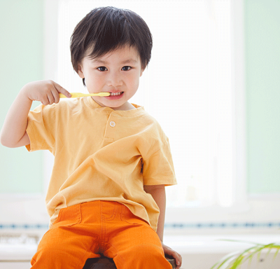 Young boy sitting and brushing teeth