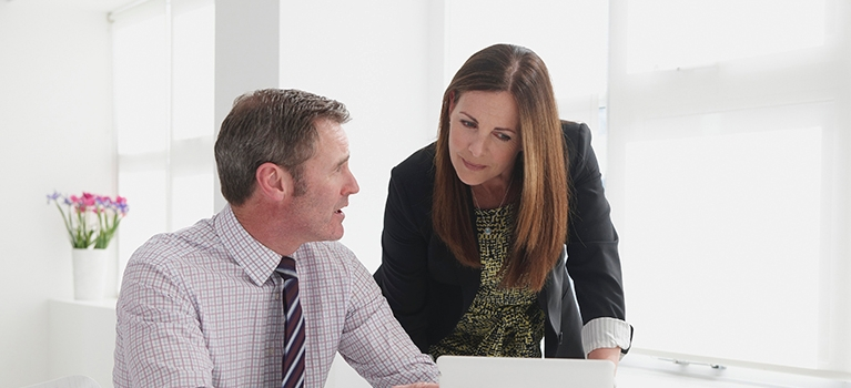 Businessman and Business woman talking near laptop