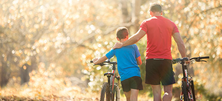 Father and son on a bike path in the woods
