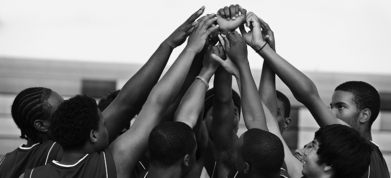 Basketball team with arms raised in huddle