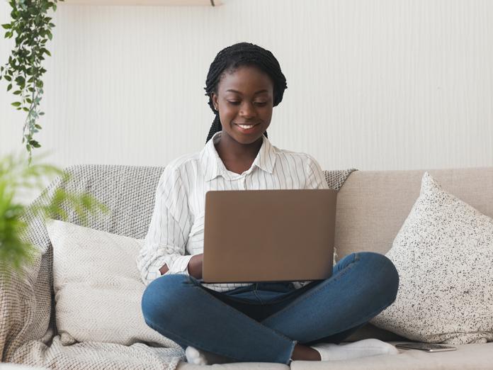 niña africana que usa el ordenador portátil en el sofá en casa sonriendo
