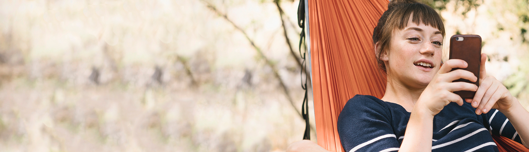 Young woman on her phone while in a hammock