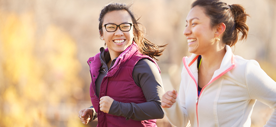 Two women jogging and smiling
