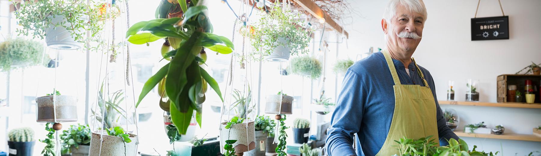 Portrait of confident terrarium shop owner holding plants
