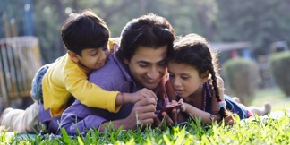 Father and Offspring Using Camcorder in Park --- Image by © Floresco Productions/Corbis