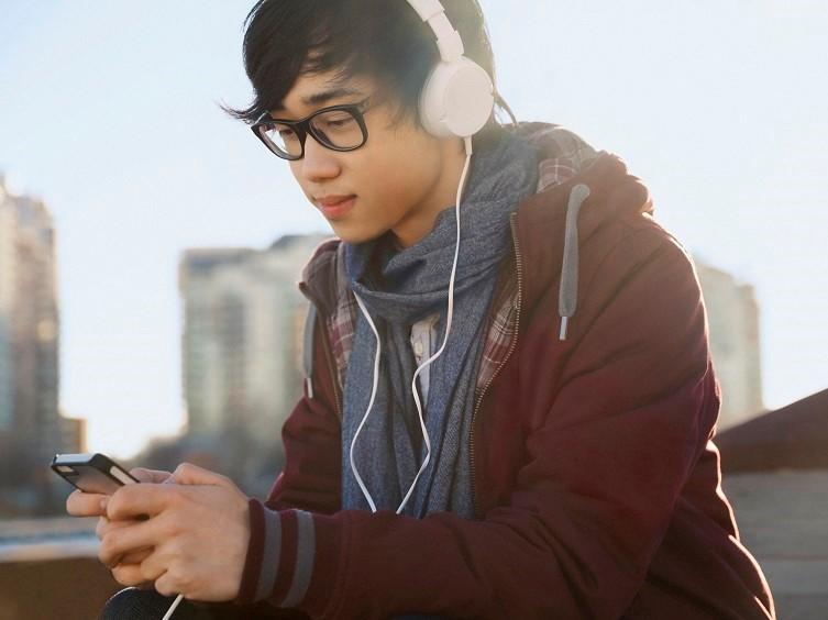 hombre joven escucha música en los teléfonos inteligentes al aire libre