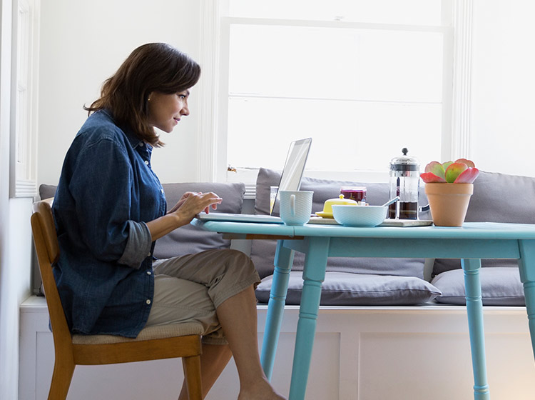 woman on laptop at kitchen table