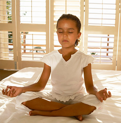 girl meditating on bed