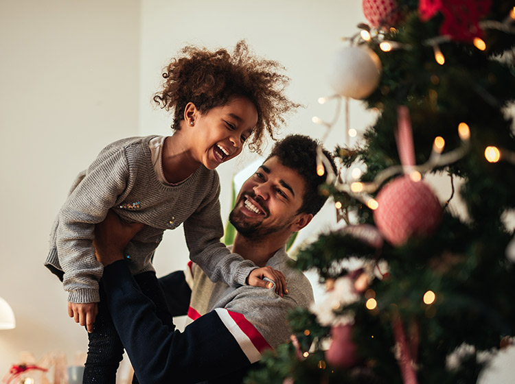 Man holding child in front of Christmas tree