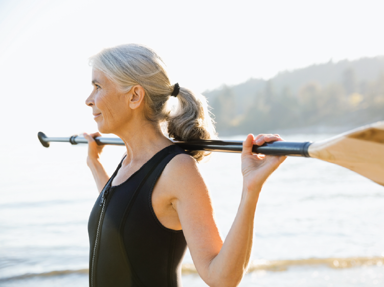 Woman outdoors holding paddle and looking at lake