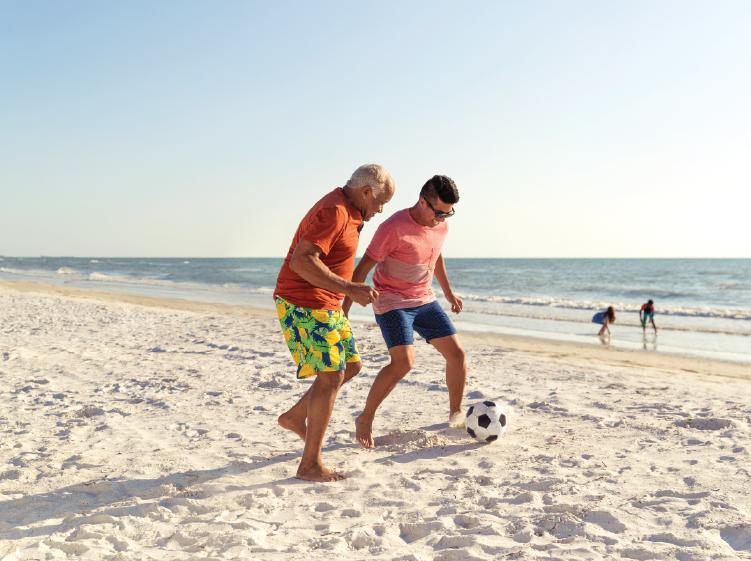 La gente que juega al fútbol en la playa
