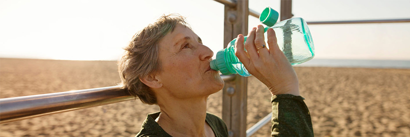 Older woman on beach drinking from water bottle