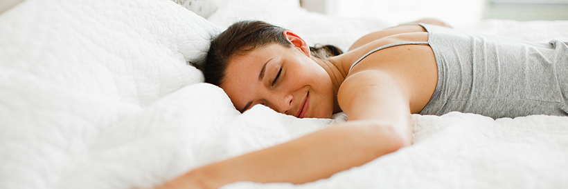 Woman in bed, eyes closed and smiling