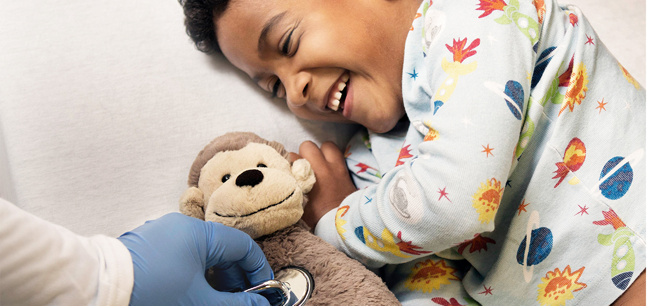 Young boy smiling with toy at the doctor
