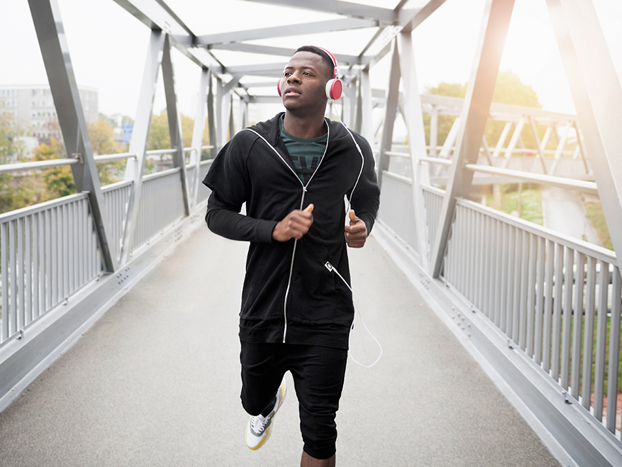 Young man running outdoors, wearing headphones