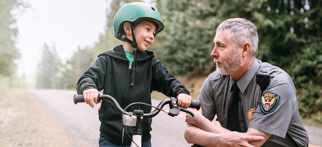 Law enforcement officer kneeling and talking to a boy on a bike