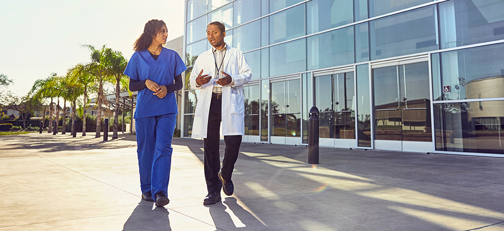 two african-american health care providers walking and speaking
