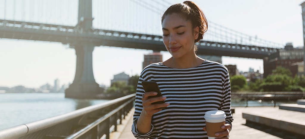 Young woman with coffee looking at her smartphone