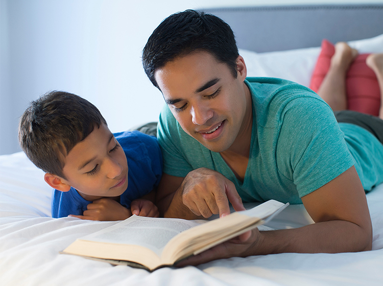 Father and son reading on bed